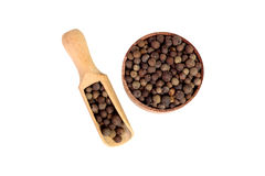 Allspice in a wooden bowl. Black pepper. Spice. isolated on white background Stock Photos