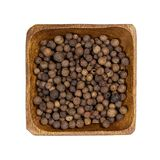 Allspice in wooden bowl isolated on white. Background. Top view stock photo