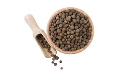 Allspice in wooden bowl and scoop isolated on white background. top view. Spices and food ingredients.  stock image