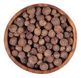Allspice in a wooden bowl on a white Stock Images