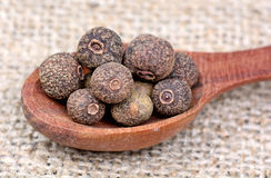 Allspice in a wooden spoon. On table royalty free stock image