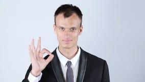 Allt är reko! Lycklig ung man som gör en gest det reko tecknet och att le Arkivbild