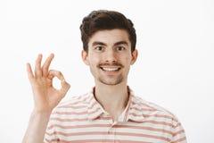 allt okay Studioskott av den gladlynta vänskapsmatch-seende caucasian grabben med mustaschen och skägget som lyfter handen med royaltyfria foton