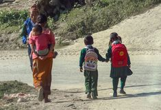 Alltagsleben in Nepal, Kinder in der Uniform gehen Hand in Hand zur Schule, Mutter trägt ein kleines Kind auf ihr zurück lizenzfreie stockfotos