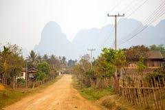 Alltagsleben von Dorf Vang Vieng mit Kalksteinbergen, Laos Stockfotografie