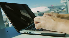 Alltid förbindelse Man maskinskrivningtext på bärbara datorn mot fönsterflygplatsen arkivfilmer