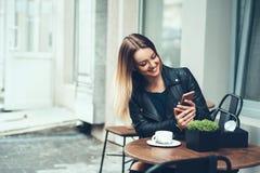 Alltid lyckligt att meddela med vänner Härligt sammanträde för ung kvinna i kafémaskinskrivningmeddelande till hennes vän, medan  arkivbilder