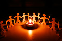 Alltogheter for peace. Some paper dolls around a candle stock images