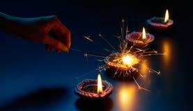 Allumage d'un cierge magique avec la lampe de diya image libre de droits