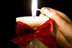 Allumage d'une bougie de Noël photo stock