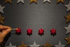 Allumage d'une bougie sur l'ardoise avec le cadre d'étoile Image stock