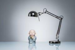 Allumage vers le haut d'étudier le moine bouddhiste de lecture avec la lampe de bureau Image libre de droits