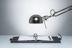 Allumage vers le haut de l'écriture de journal intime de carnet avec la lampe de bureau Photographie stock libre de droits
