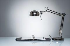 Allumage vers le haut de l'écriture de journal intime de carnet avec la lampe de bureau Image stock