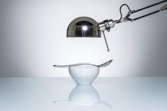 Allumage vers le haut de la cuillère d'argent en céramique blanche de cuvette avec la lampe de bureau Photo stock