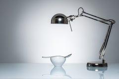 Allumage vers le haut de la cuillère d'argent en céramique blanche de cuvette avec la lampe de bureau Images libres de droits