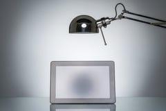 Allumage vers le haut de la note de touchpad de comprimé avec la lampe de bureau Photos stock