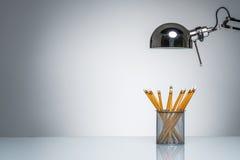 Allumage vers le haut de la papeterie orange de support de crayon avec la lampe de bureau Images stock