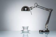 Allumage vers le haut de la tasse de café blanche de tasse avec la lampe de bureau Photos stock