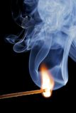 Allumette brûlante au-dessus d'un fond noir, avec de la fumée Image stock