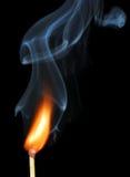 Allumette brûlante avec de la fumée sur le noir Image stock