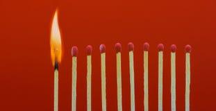 Allumettes brûlantes mettant le feu à ses voisins Photographie stock libre de droits