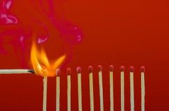 Allumettes brûlantes mettant le feu à ses voisins Photo libre de droits