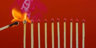 Allumettes brûlantes mettant le feu à ses voisins Photos libres de droits