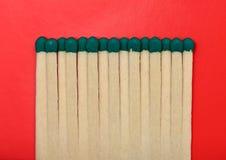 Allumettes d'isolement sur un fond texturisé rouge. Photographie stock