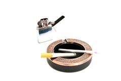 Allumeur et deux cigarettes dans le cendrier Image stock