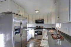 Allumez la petite cuisine compacte remplie de caractéristiques intérieures à la maison photographie stock