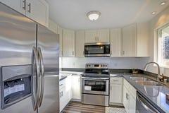 Allumez la petite cuisine compacte remplie de caractéristiques intérieures à la maison photo libre de droits