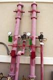Allumez les pipes d'arroseuse sur l'extérieur d'une construction Image libre de droits