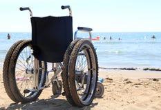 alluminio della sedia a rotelle sulla sabbia della spiaggia Fotografia Stock Libera da Diritti