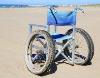alluminio della sedia a rotelle sulla sabbia della spiaggia Fotografia Stock