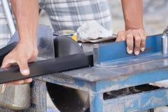 Alluminio di taglio del lavoratore con la lama della smerigliatrice Fotografie Stock