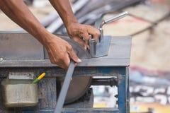 Alluminio di taglio del lavoratore con la lama della smerigliatrice Fotografia Stock