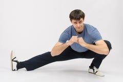 Allungamenti accovacciantesi dell'atleta i muscoli di giusta gamba Immagine Stock