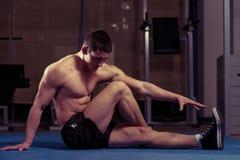Allungamenti atletici dell'uomo Fotografie Stock Libere da Diritti