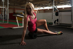 Allungamenti atletici della donna con il rullo in palestra Immagini Stock