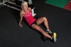 Allungamenti atletici della donna con il rullo in palestra Fotografia Stock