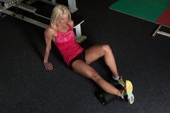 Allungamenti atletici della donna con il rullo in palestra Immagine Stock Libera da Diritti