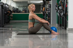 Allungamenti atletici della donna con la palla Fotografia Stock