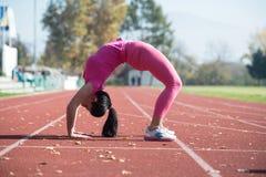 Allungamenti atletici della donna nell'area del parco della città Fotografia Stock Libera da Diritti