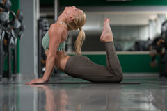 Allungamenti atletici della donna in palestra Fotografia Stock