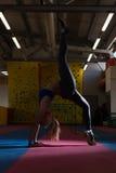 Allungamenti atletici della donna in palestra Fotografia Stock Libera da Diritti