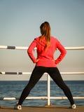 Allungamenti del pareggiatore della donna sul pilastro dalla spiaggia Fotografie Stock