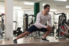 Allungamenti dell'uomo di forma fisica al pavimento Fotografie Stock Libere da Diritti