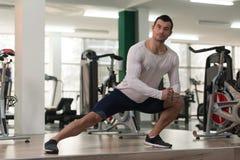 Allungamenti dell'uomo di forma fisica al pavimento Fotografie Stock