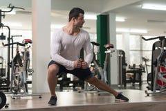 Allungamenti dell'uomo di forma fisica al pavimento Fotografia Stock Libera da Diritti